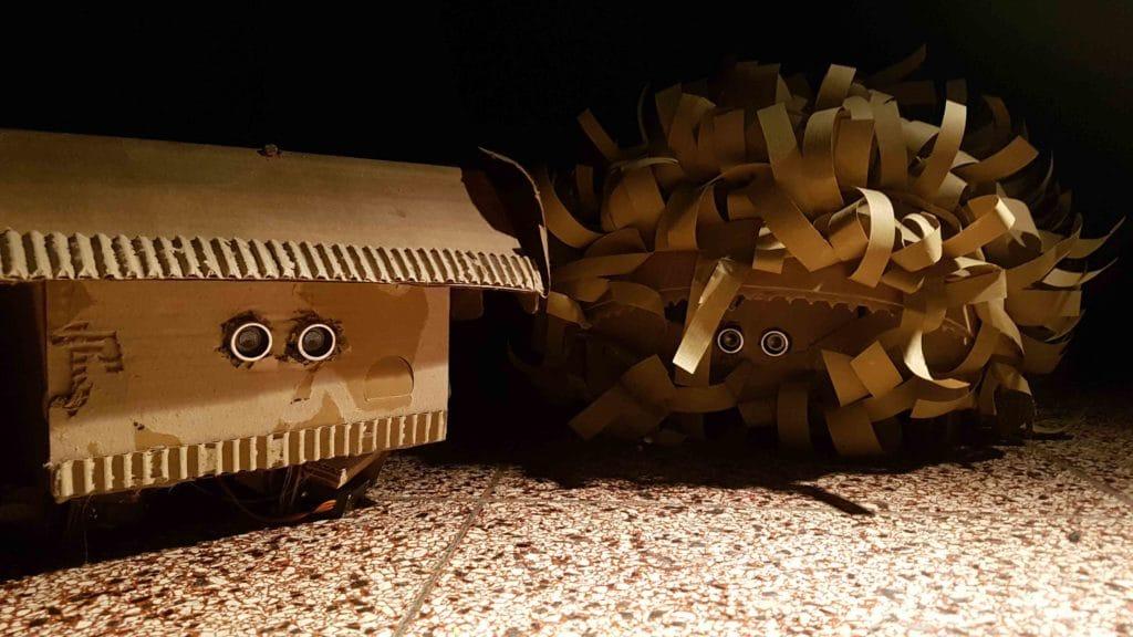 Medienkunst mit Robotern: Zwei kleine Roboter aus Packpapier und Pappe