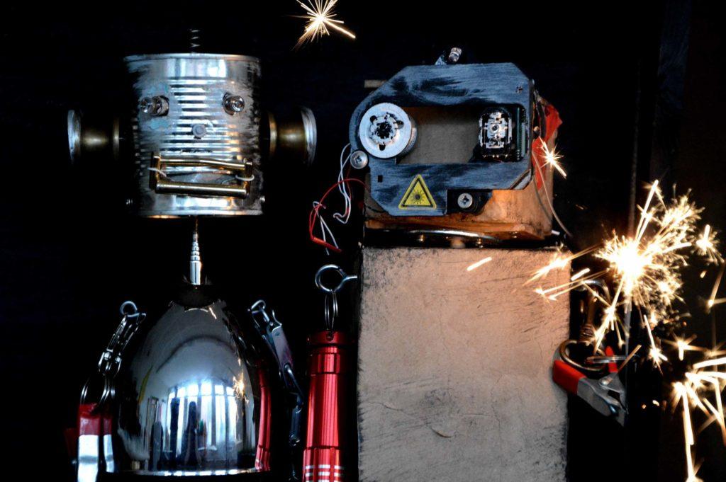 """Puppentheater mit Robotern: Das Bild zeigt zwei Roboter aus dem Puppentheaterstück """"Strom - Eine Robotergeschichte"""" mit einer Wunderkerze"""