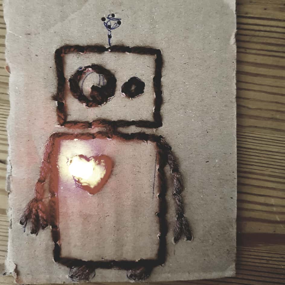 E-Textiles_Workshop: Das Bild zeigt einen auf pappe gestickten kleinen Roboter mit einem LED-Herz, das leuchtet.