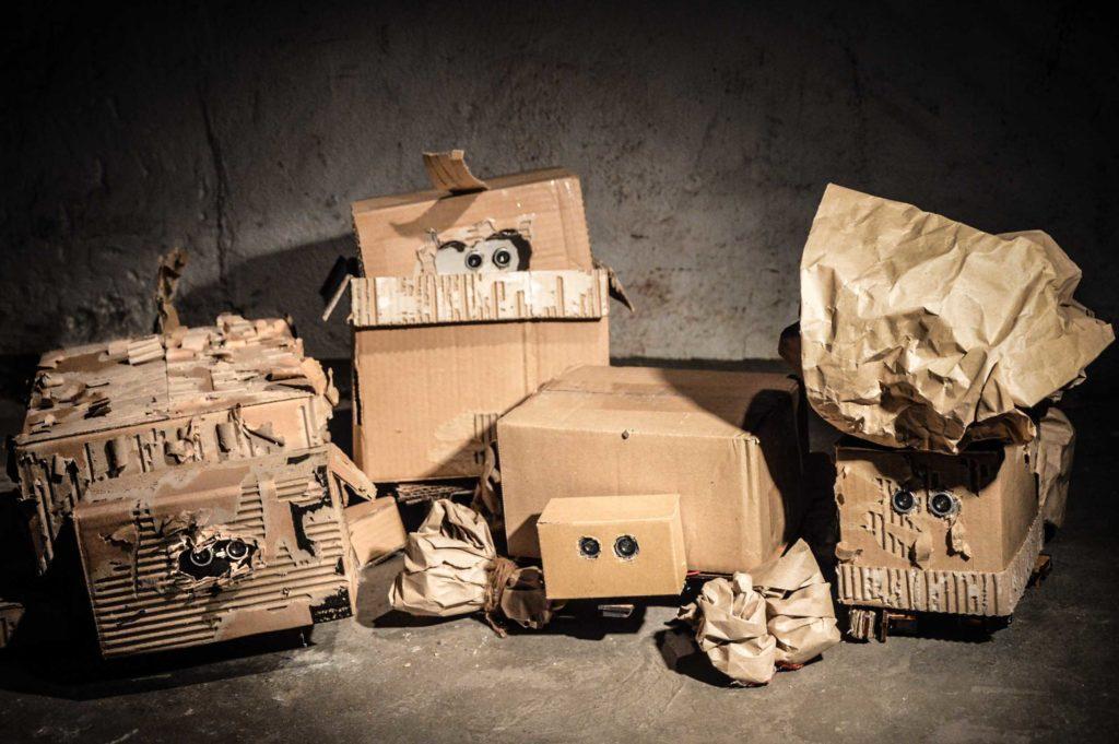 """Medienkunst: Das Bild zeigt vier Roboter aus Pappe aus der Installation """"Ein Platz an der Sonne""""."""