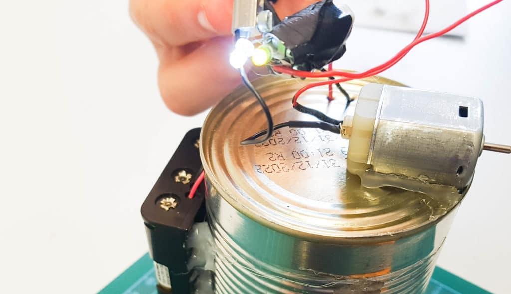 Technik:Workshops: Ein Kind zeigt die leuchtenden LEDs an seinem DIY Roboter.